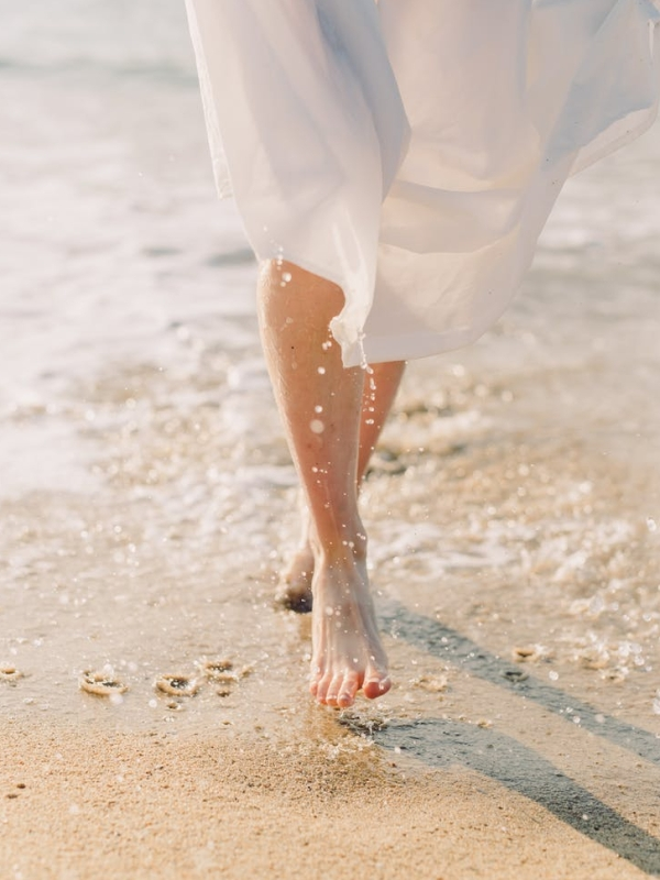 Waist down of a woman in a white dress walking in shallow water on the beach.
